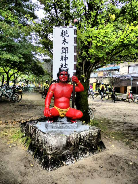 A concrete oni statue greets visitors near the first torii gate