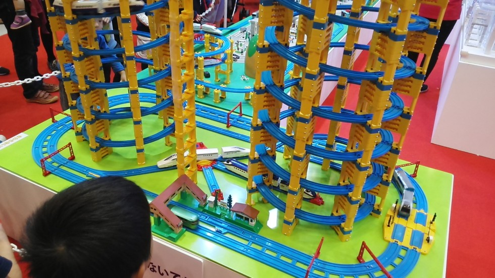 A wide-eyed child is eager to play with this tall Pla-rail layout at the 2015 Tokyo Motor Show