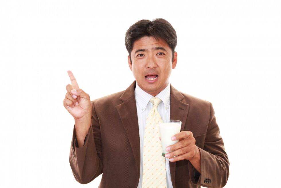 Photo of an asian man holding a glass of milk