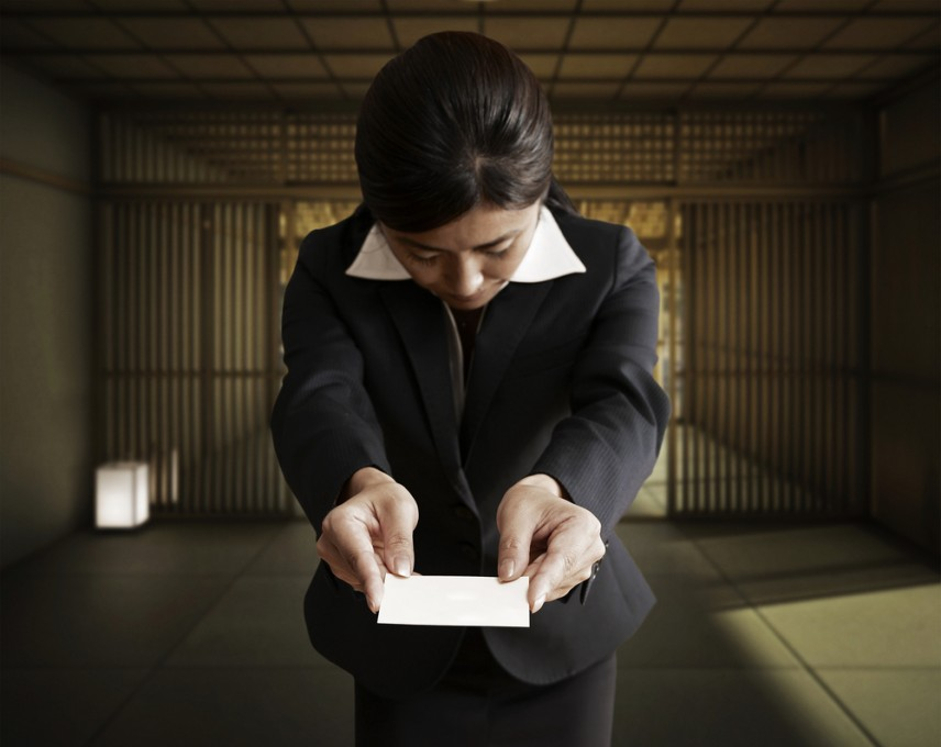 Japanese woman handing a business card