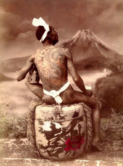 Tattooed man sitting on a casket of Sake