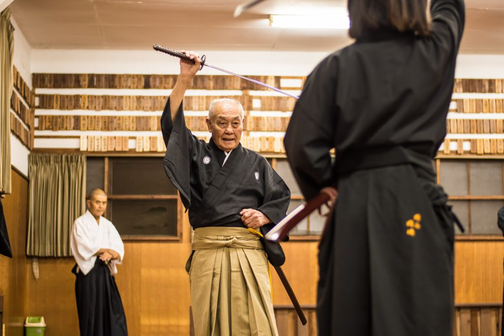 iaido master teaching his pupil how to use a katana