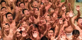 People huddled in a temple, extending their hands